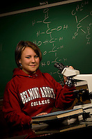 A female college student works in the biology lab with a microscope at a college in Belmont, NC.