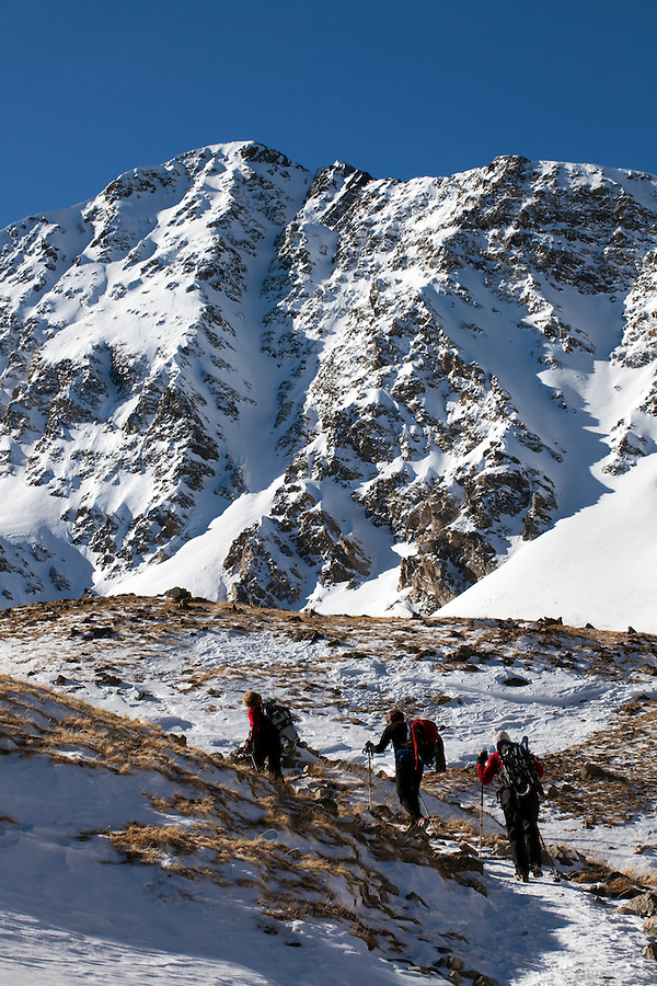 Three climbers head through Stevens Gulch on their way to the slopes of Torreys Peak, Colorado.