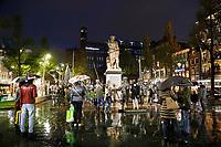Nederland Amsterdam 2017 .  Regen in Amsterdam. Toeristen fotograferen Rembrandt en de bronzen Nachtwacht, op het Rembrandtplein. Foto Berlinda van Dam / Hollandse Hoogte