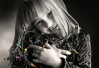 Black & white image of a little girl holding a string of Christmas lights; the lights are in color.