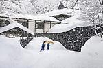_DSC6733, Vacheron, Japan, 02/2016, JAPAN-10267. Men with yellow umbrellas walk in the snow.<br /> <br /> CHECK IMAGE USAGE<br /> <br /> IG: Tsurunoyu, Japan, 2016. 12/25/2017<br /> <br /> FINAL_Vacheron<br /> <br /> retouched_Ekaterina Savtsova, Sonny Fabbri 5/8/2017