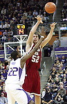 Caleb Forrest (#52) passes to an open teammate despite the defensive pressure applied by Justin Holiday (#22) during the Cougars Pac-10 conference showdown with the University of Washington on March 7, 2009, in Seattle, Washington.  Both teams came in to the game on a roll, and in a hard fought battle, the Huskies prevailed 67-60 to wrap up the regular season Pac-10 championship.