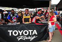 Mar. 10, 2012; Gainesville, FL, USA; NHRA funny car driver Jeff Arend (center) and Cruz Pedregon (right) signs autographs and greets fans during qualifying for the Gatornationals at Auto Plus Raceway at Gainesville. Mandatory Credit: Mark J. Rebilas-