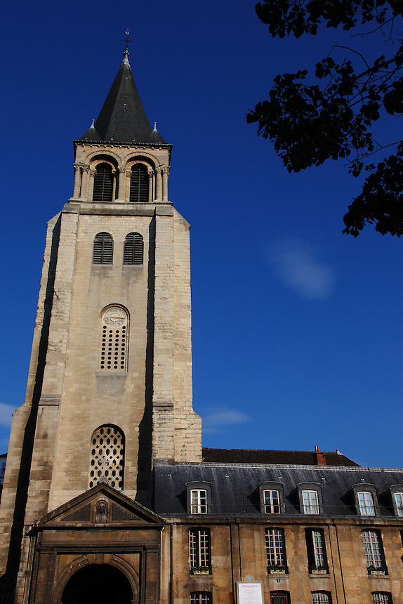 A front view of the top of the church of Saint Germain in Paris, with its bell tower and the foliage of a tree, in a sunny spring day. Digitally Improved Photo.