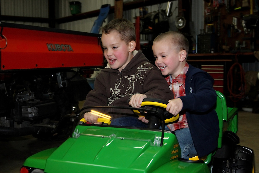 Aidan & Eli taking their first test spin in a kiddie John Deere.