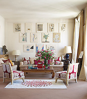 The living room is furnished with a pair of custom-made sofas and vintage parchment-covered chairs and the rug is a de Gunzburg design
