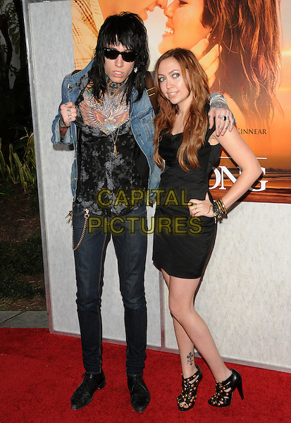 "TRACE CYRUS & BRANDI CYRUS .at the Touchstone Pictures' World Premiere of ""The Last Song"" held at The Arclight  in Hollywood, California, USA, March 25th 2010.           .arrivals full length family siblings brother sister black dress tattoos denim jacket sunglasses jeans shirt gold studded sandals shoes studs hand on hip bracelets                            .CAP/RKE/DVS.©DVS/RockinExposures/Capital Pictures"
