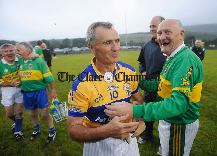 Noel Roche and Paudie Neylon embrece following the Clare GAA 125 anniversary match in Carron. Behind is former Clare manager John Maughan. Photograph by John Kelly.