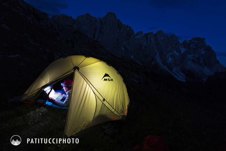 A woman using a headlamp to read a map is seen inside her tent at night
