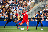 Danny Koevermans (14) of Toronto FC strikes the ball as Amobi Okugo (14) and Carlos Valdes (2) of the Philadelphia Union defend. The Philadelphia Union defeated Toronto FC 3-0 during a Major League Soccer (MLS) match at PPL Park in Chester, PA, on July 8, 2012.