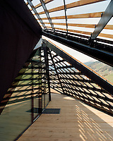 Panels of latticed larch wood shield the wooden balcony from the snow