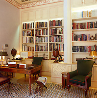 An elegantly furnished study/library has built in cupboards above the wall to wall bookcases