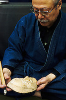 Kitagawara Seiun carving a female mask.