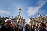 Città del Vaticano, 24 Febbraio, 2013. Fedeli mostrano un crocifisso in Piazza San Pietro.