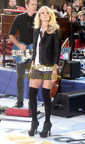 """CARRIE UNDERWOOD.performs live on the NBC's """"TODAY"""" Show live from Rockefeller Center, New York, NY, USA, 30th July 2010..music country live on stage concert gig.full length  black jacket blazer white shirt tie grey gray shorts otk over the knee high socks platform studded ankle boots heels booties .CAP/ADM/AC.©Alex Cole/AdMedia/Capital Pictures."""