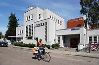 Nederland  Amsterdam - 2017. Postbezorger in Betondorp. Servicepunt het Brinkhuis.  Betondorp is een buurt in het Amsterdamse stadsdeel Oost. De buurt werd als tuindorp gebouwd in de Watergraafsmeer tussen 1923 en 1925 als Tuindorp Watergraafsmeer. Doordat voor het eerst veel beton werd toegepast bij de bouw van de woningen, ging het in de volksmond al snel Betondorp heten.   Foto Berlinda van Dam / Hollandse Hoogte