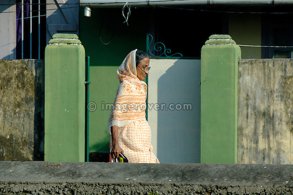 India, Kerala, Fort Cochin (Cochi, Kochi). Elderly indian woman in sari walking down a street in Cochin. No releases available.
