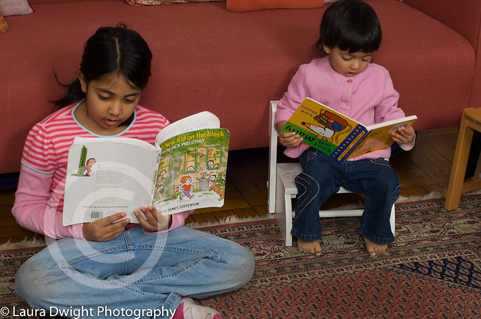 imitation modeling 16 month old toddler girl looking at book, holding it upsdide down,  while 7 year old sister reads nearby
