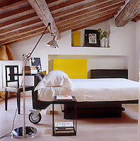 The attic bedroom has a contemporary bed that incorporates a simple desk into its headboard