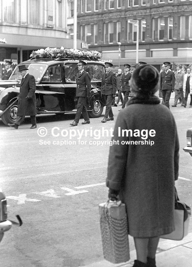 A shopper pauses to pay her respects as the funeral of Constable David Montgomery passes through the city centre in Belfast, N Ireland on 29th January 1972. Constable Mongomery, along with another police officer, Sergeant Peter Gilgun, died in a Provisional IRA gun attack on 27th January 1972 on Creggan Road, Londonderry.  Constable Montgomery had been due for a transfer from Londonderry but had been allowed to stay on until June when he planned to marry a 19 year old local girl. 197201290063b<br />