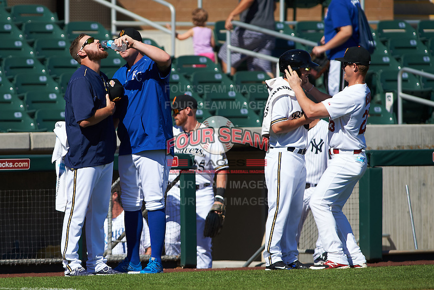 Surprise Saguaros Adrian Houser (left) gets a drink from teammate Brooks Pounders as Nate Orf gets some assistance putting on a helmet from Patrick Wisdom (23) during a pre-game standoff prior to an Arizona Fall League game against the Glendale Desert Dogs on October 23, 2015 at Salt River Fields at Talking Stick in Scottsdale, Arizona.  Glendale defeated Surprise 9-6.  (Mike Janes/Four Seam Images)