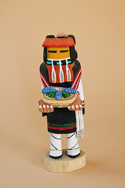 Hopi kachina doll carved from cottonwood depicts the corn maiden dressed in traditional dance regalia offering a basket of blue corn and cactus fruit to signify abundant crops