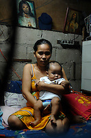 Heidi Mission, 23, with her recently born baby poses in her home. she has three children so far. She lives in the slum area of Manila called San Anreas Bukid (neighbour-hood) where families commonly have between 6- 12 children. There is no family planning available from the Government due to a law passed by the Mayor and they are too poor to pay for their own contraception.