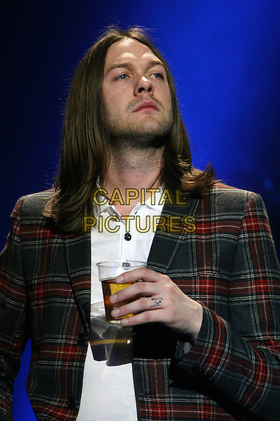 KASABIAN -Tom Meighan .Performing live at the R.A.Hall as part of the concerts in aid of Tennage Cancer Trust, Royal Albert Hall, London, England..March 27th, 2009.stage concert gig music band half length drink beverage red tartan plaid jacket grey gray tattoo .CAP/MAR.© Martin Harris/Capital Pictures.