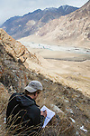 Snow Leopard (Panthera uncia) biologist, David Cooper, taking down data on snow leopard kill site, Sarychat-Ertash Strict Nature Reserve, Tien Shan Mountains, eastern Kyrgyzstan