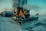 Alaska, Prudhoe Bay, oilfields, A D-9 Caterpillar tractor, winterized for Arctic work, North Slope, Alaska, Arctic drilling rig in the background