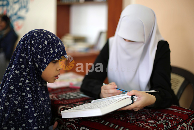 A Palestinian woman reads with a young girl from a copy of the Koran, Islam's holy book, at a religion school in Gaza City on June 21, 2016, during the Muslim fasting month of Ramadan. Photo by Mohammed Asad
