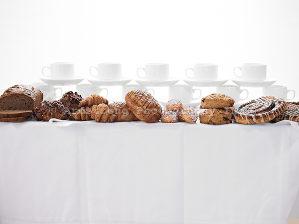 A large assortment of baked goods and stacked coffee cups with saucers, on a buffet table with white table cloth.