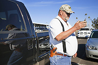 "USA. Arizona state. Phoenix. Don Carter stands close to his pickup truck in a parking-lot. He just came out of the Crossroads of the West Gun Show. Don Carter is an everyday supporter of openly carrying a firearm in public. Today he carries a Walter P99 in his belt's holster. The Walther P99 is a semi-automatic pistol developed by the German company Carl Walther GmbH Sportwaffen as a replacement for the Walther P5 and the P88. In the United States, open carry refers to the practice of ""openly carrying a firearm in public"", as distinguished from concealed carry, where firearms cannot be seen by the casual observer. A firearm is a portable gun, being a barreled weapon that launches one or more projectiles often driven by the action of an explosive force. Most modern firearms have rifled barrels to impart spin to the projectile for improved flight stability. The word firearms usually is used in a sense restricted to small arms (weapons that can be carried by a single person). The right to keep and bear arms is a fundamental right protected in the United States by the Second Amendment of the Bill of Rights in the Constitution of the United States of America and in the state constitutions of Arizona and 43 other states. 24.01.16 © 2016 Didier Ruef"