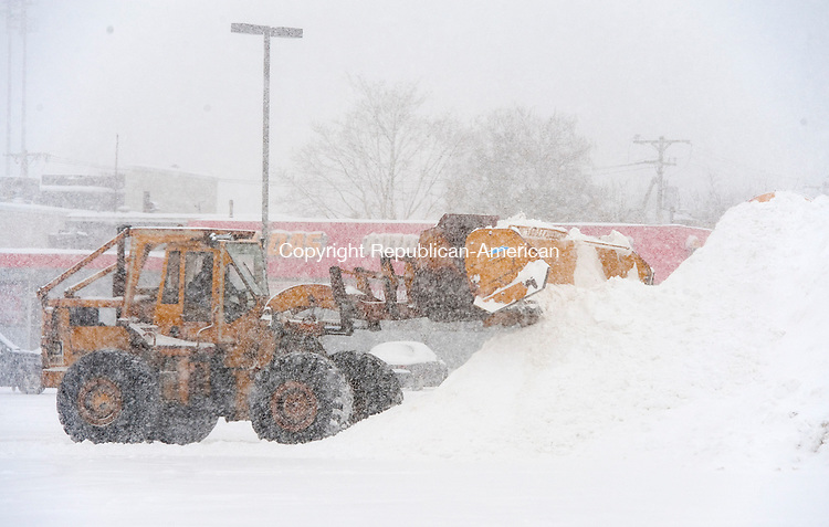 TORRINGTON, CT-021314JS06- A front loader dumps snow into a pile while clearing the parking lot of the Torrington Plaza as Thursday's snowstorm rolled through the area. <br /> Jim Shannon Republican-American