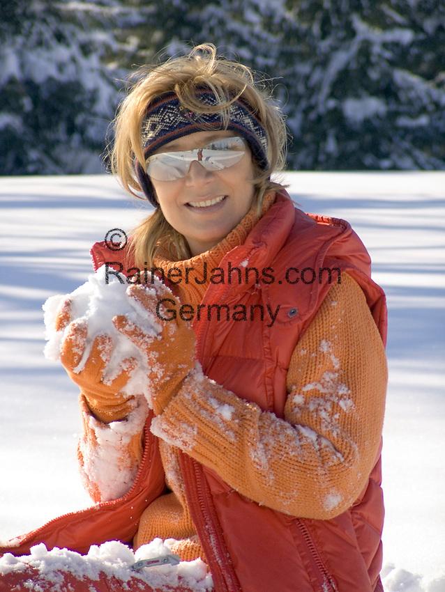 Deutschland, Frau sitzt im Schnee mit Schneeball   Germany, woman with snowball sitting in the snow