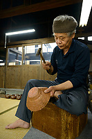 "Goro Hosono, ""tsuiki"" copperware artisan working on a copper kettle. Gyokusendo, Tsubame, Niigata Pref, Japan, August 24, 2017. Traditional copper metalworking company Gyokusendo was founded in 1816 and is a registered as a traditional craft of Japan. At Gyokusendo, in a highly-skilled craft process, complex items such as teapots are beaten from a single sheet of copper using hammers and hundreds of other specialist tools."