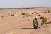 A Chinese afforestation worker rests near straw stacks in the desert areas of Minqin county in Gansu province, October 2016. Locals poke straw partway into the sand, forming a pattern of small squares. The grid like network of straw fences break the force of the wind at ground level, stopping dune movement by confining the sand within the squares of the grid. Minqin county is located in between the Tengger Desert and the Badain Jaran Desert.