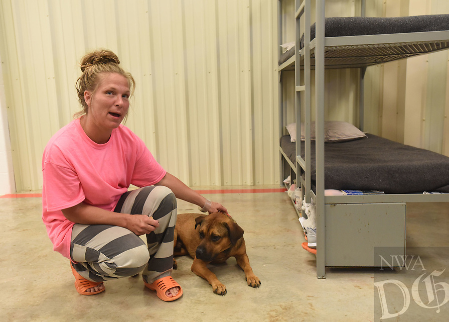 NWA Democrat-Gazette/FLIP PUTTHOFF <br />Tanis Whaley, an inmate at the Benton County Jail, pets on Tuesday July 11 2017 Mr. Bean, a New Leash on Life canine.