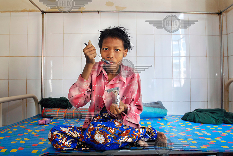 29-year-old Poeun Pech, an HIV positive mother of two boys, eats a therapeutic food to counter malnourishment (Plumpy'nut, a peanut-based high protein famine relief food) at a hospital in Pourk District. Her husband left her when he discovered her status and she returned to live with and be looked after by her parents. She has to travel to the hospital for treatment and to receive a supply of ARVs and the travel costs are a prohibitive USD 5 per person.