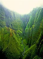 Aerial of waterfalls in green lush rainforest valley on the island of Kauai
