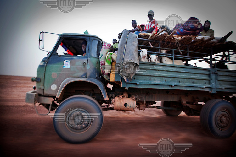 A truck carries passengers through the desert towards the capital city of Niamey.