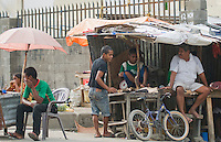 People sell a variety of fruits, vegetables, and other goods at a sidewalk market in Dili, Timor-Leste (East Timor)