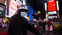 "NEW YORK, NEW YORK - MARCH 5: A man wears a facial mask while crossing Times Square on his bicycle on March 5, 2020. in New York City. The state of New York has 44 people in quarantine, about 4,000 people are in ""precautionary"" quarantine in more than two dozen counties, including more than 2,700 in the city and 1,000 in Westchester, Cuomo said. (Photo by Pablo Monsalve / VIEWpress via Getty Images)"