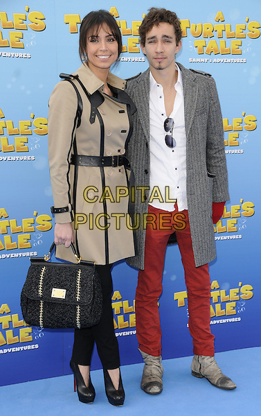 "CHRISTINE BLEAKLEY & ROBERT SHEEHAN .At ""A Turtle's Tale: Sammy's Adventures 3D"" UK Premiere, BFI Southbank,  London, England, UK, March 20th 2011..full length red jeans hand fingerless gloves grey gray coat white shirt goatee facial hair tweed booties shoes shooboots black handbag bag beige leather trench coat belt  christian louboutin .CAP/CAN.©Can Nguyen/Capital Pictures."
