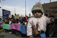 Pictured: A young baby is held by his father wjo join other protesters with placards gather in Piraeus port Tuesday 08 March 2016<br /> Re: Afghan migrants hold a protest at Piraeus port, near Athens, Greece.
