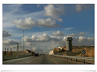 A portion of Road 443 surrounded by wall, decorated by picturesque murals, fences and watching towers blocking the Palestinian villages from the road..Road 443 is one of the main throughways of the West Bank. Its overall length is 25.5 KM, 14 out of which run through the heart of the West Bank. .With the break of the second Intifada at the end of 2000, Israel had severely restricted Palestinian movement on road 443, which was their main road from the Beit Sira, Saffa, Beit Liqiya, Kharbatha al-Misbah, Beit Ur al-Tahata, Beit Ur al-Foqqa and al-Tira villages to Ramallah. These restrictions were harshened in 2002, when Palestinian movement was completely prohibited. In recent years all entries and exits from the road to the area's villages were blocked with gates and concrete slabs. Photo by Quique Kierszenbaum