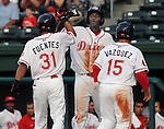 Outfielder Vladimir Frias (29), center, high-fives outfielder Reymond Fuentes (31) after both scored against the Augusta GreenJackets in a game on May 20, 2010, at Fluor Field at the West End in Greenville, S.C. First baseman Christian Vazquez (15) is at right.