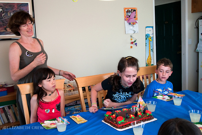 Berkeley CA Girl, blowing out birthday candles at her eighth party while brother,Chinese friend and mother look on  MR
