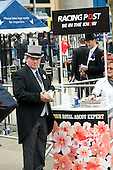 A man in a top hap buys the Racing Post at Ascot racecourse.