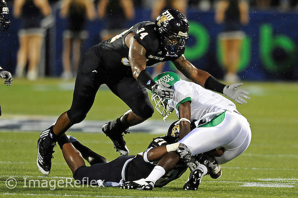 1 September 2011:  FIU linebacker Winston Fraser (34) and defensive back Chuck Grace (21) combine to tackle North Texas running back James Hamilton (2) in the first half as the FIU Golden Panthers defeated the University of North Texas, 41-16, at University Park Stadium in Miami, Florida.